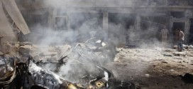 The wreckage of a burnt car is seen as people inspect a site hit by what activists said was a barrel bomb dropped at Qadi Askar district of Aleppo
