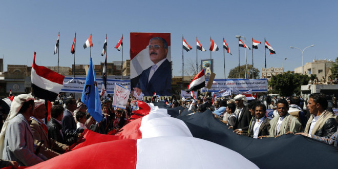 Supporters of Yemen's former President Ali Abdullah Saleh hold a huge Yemeni flag next to a poster of Saleh as they rally in his support in Sanaa