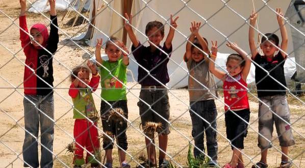 Syrian refugee children flash V-signs at