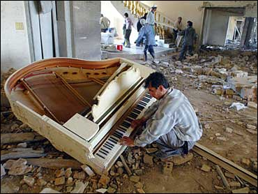 Iraqi man playing piano in middle of destruction (2003)