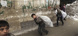 Children carry goods at the Karaj al-Hajez crossing in Aleppo