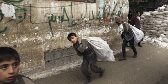 Children carry goods at the Karaj al-Hajez crossing in Aleppo