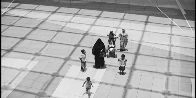 A female employer and her children are accompanied by their domestic worker, back right, as they walk through The Avenues, an indoor luxury shopping center in Kuwait City.  © 2010 Moises Saman/Magnum Photos