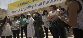 In this photo taken Wednesday, May 27, 2015, Arab Israeli Christians hold signs during a demonstration in front of the education ministry in Jerusalem. (AP Photo/Sebastian Scheiner)