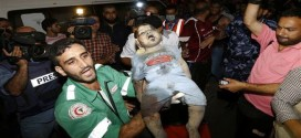 A Palestinian doctor holds the dead body of a baby girl following an Israeli airstrike on a house in Gaza City on August 19, 2014.